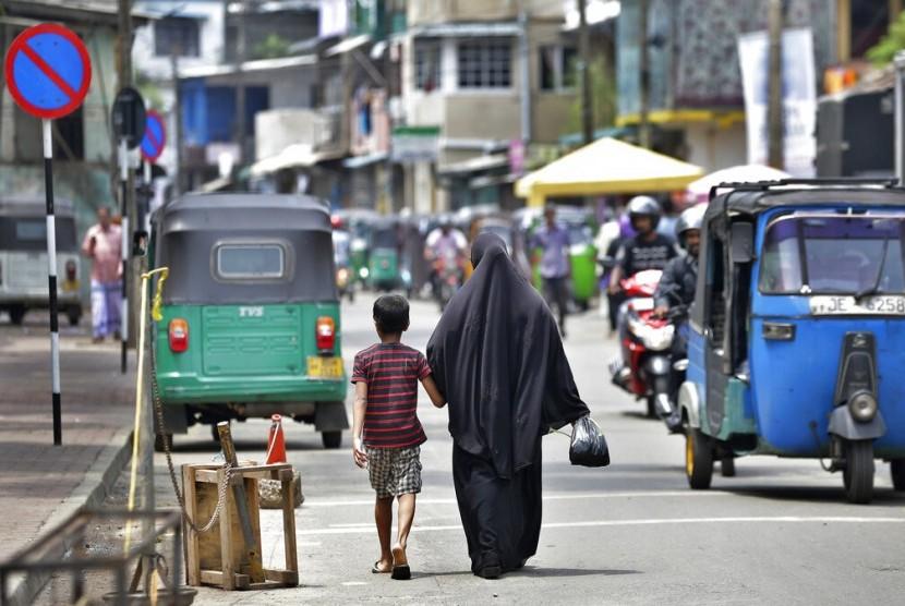 Seorang Muslim Sri Lanka dan putranya berjalan setelah dari pasar di Kolombo, Sri Lanka, Senin (29/4). Sri Lanka resmi melarang penggunaan cadar.