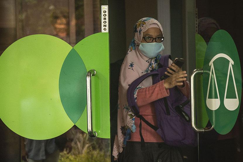 Seorang nasabah berjalan keluar seusai melakukan transaksi di Kantor Pusat Pegadaian, Jakarta, Kamis (7/6).