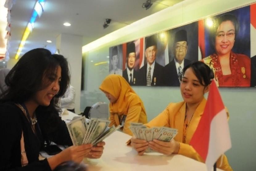 Seorang nasabah bersama dengan pegawai Bank Mandiri sedang menghitung uang lembaran dolar AS di Jakarta, Rabu (12/8).