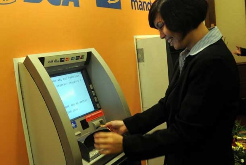 Seorang nasabah menarik uang tunai dari ATM (Ilustrasi)