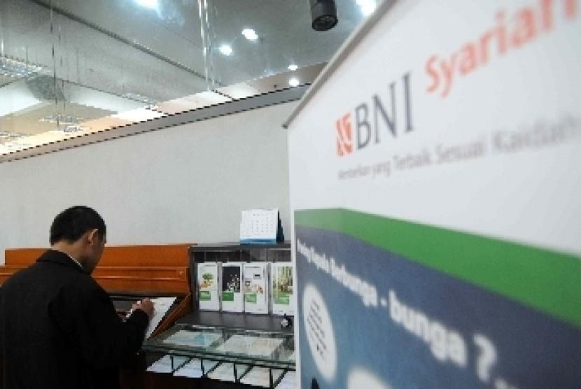 Seorang nasabah mengisi slip setoran tabungan di kantor layanan BNI Syariah, Jakarta.