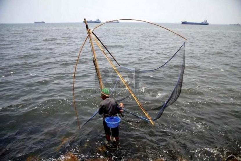 Seorang nelayan mengangkat jaring di wilayah pesisir pantai. (ilustrasi)