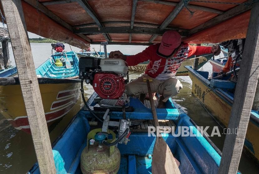 Seorang nelayan menyalakan mesin perahu yang telah dikonversi menggunakan bahan bakar elpiji.