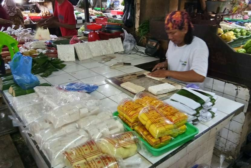 Seorang pedagang, Becky (30 tahun) di Pasar Tebet Barat, Kamis (6/9) tengah mengiris tempe untuk dibungkus dengan daun pisang. Harga tempe dan tahu belum mengalami kenaikan meski rupiah terus melemah dan memicu kenaikan harga kedelai impor. Pedagang memilih untuk mengecilkan ukuran agar keuntungan yang diperoleh tetap sama.