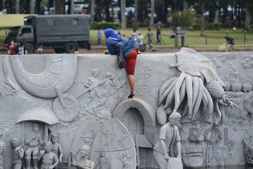 Seorang Pedagang Kaki Lima (PKL) kalang kabut menaiki tembok pembatas, saat melarikan diri dari kejaran Satpol PP di kawasan Monumen Nasional (Monas).