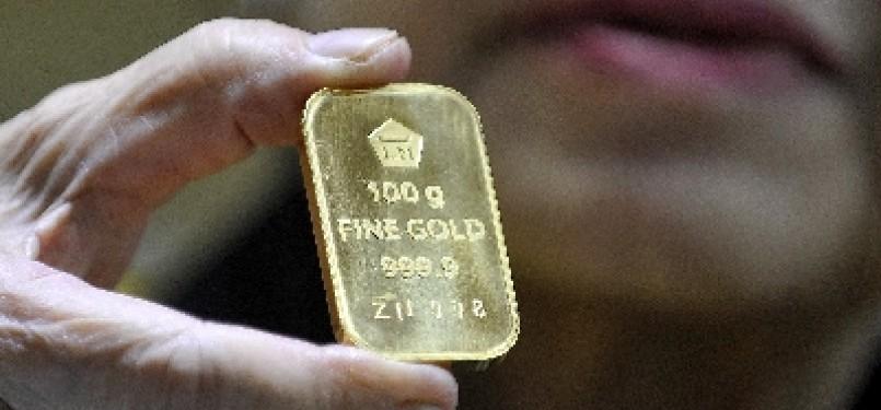 Seorang pedagang menunjukkan emas batangan.