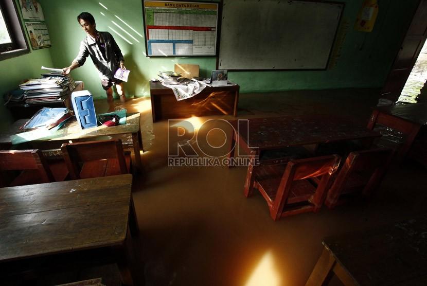 Seorang pegawai Tata Usaha merapihkan dokumen di ruang kelas SD Jatimekar IX, Jatiasih, Bekasi, Jawa Barat, Kamis (18/4).   (Republika/Adhi Wicaksono)