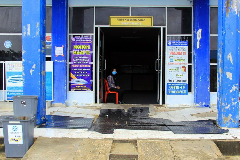 Seorang pekerja berjaga di pintu masuk terminal penumpang antar pulau (ilustrasi)