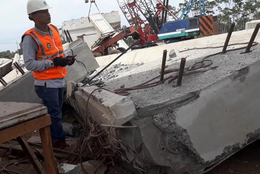 Seorang pekerja melihat konstruksi bangunan Proyek Strategis Nasional (PSN) Tol Pasuruan  Probolinggo (Paspro) yang ambruk di Desa Cukurgondang, Grati, Pasuruan, Ahad (29/10).