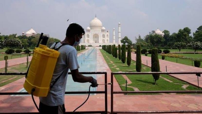 Pembatasan Dicabut, Taj Mahal Kembali Dibuka untuk Turis. Seorang pekerja membersihkan pagar di tempat Taj Mahal di Agra, India.