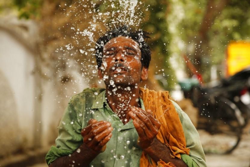 Seorang pekerja memercikkan air ke wajahnya di tengah cuaca panas di Prayagraj, Uttar Pradesh, India, Kamis (13/6). Cuaca panas ekstrem melanda India dengan rata-rata suhu mencapai 48 derajat Celcius.