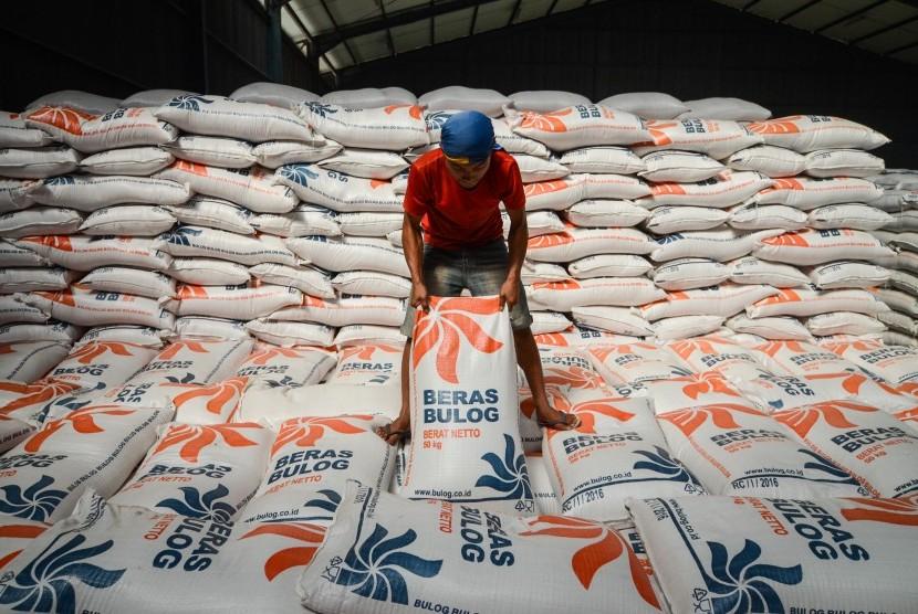 Seorang pekerja mengangkut karung beras saat melakukan bongkar muat di Gudang Bulog Baru Cisaranten Kidul Sub Divre Bandung, Jawa Barat, Selasa (3/7).