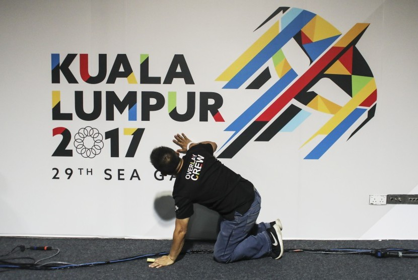 Seorang pekerja menyiapkan baligo SEA Games 2017 di media center di Kuala Lumpur, Malaysia, Jumat (11/8).