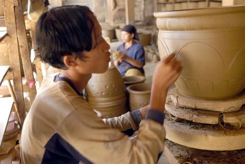 Seorang pekerja tengah memberikan sentuhan terakhir dari pembuatan sebuah pot bunga yang terbuat dari tanah liat, di sebuah industri keramik rakyat, di Plered, Kabupaten Purwakarta, Rabu (22/9).