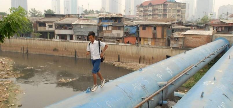 Seorang pelajar berlari melintasi pipa air milik PAM Jaya di atas Kali Krukut, Bendungan Hilir, Jakarta.
