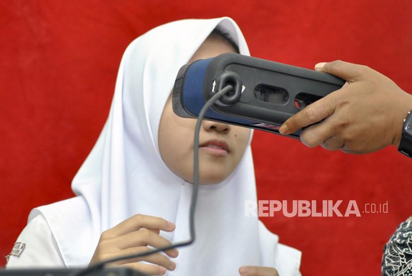 Seorang pelajar merekam data dirinya untuk pembuatan KTP elektronik saat Disdukcapil Goes To School di SMAN 9, Kelurahan Ciwaringin, Kota Bogor, Jawa Barat, Jumat (15/3/2019).