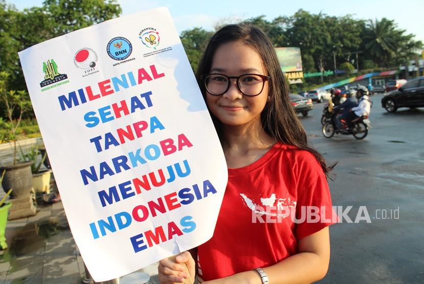 Seorang pelajar sekolah memperlihatkan poster ajakan millenial sehat tanpa narkoba saat berkampanye memperingati Hari Anti Narkotika Internasional (HANI) di Bundaran Digulis Pontianak, Kalimantan Barat, Rabu (26/6/2019).