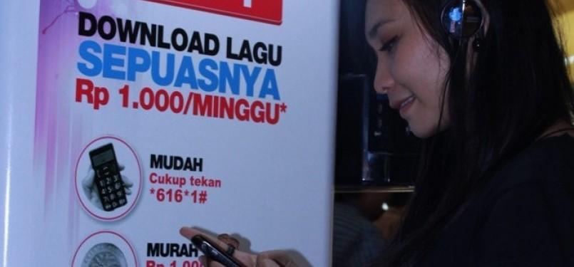 Seorang pelanggan Telkomsel sedang memanfaatkan ponselnya untuk mendengarkan lagu yang telah diunduh melalui LangitMusik HITS!.