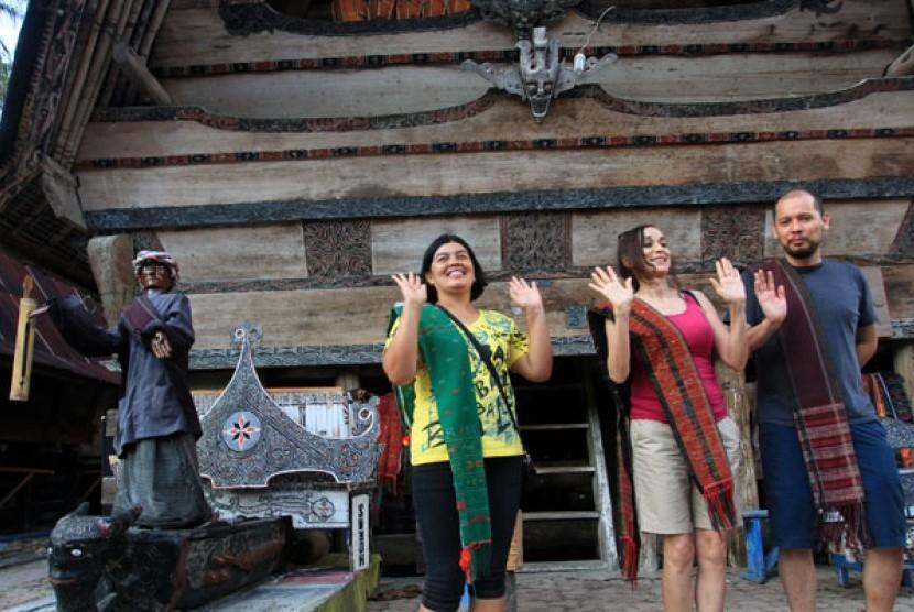 Seorang pemandu dan wisatawan mancanegara menari disamping patung Sigale-Gale, di Desa Tomok, Kecamatan Simanindo, Kabupaten Samosir, Sumut, Sabtu (24/8). Seorang pemandu dan wisatawan mancanegara menari disamping patung Sigale-Gale, di Desa Tomok, Kecamat