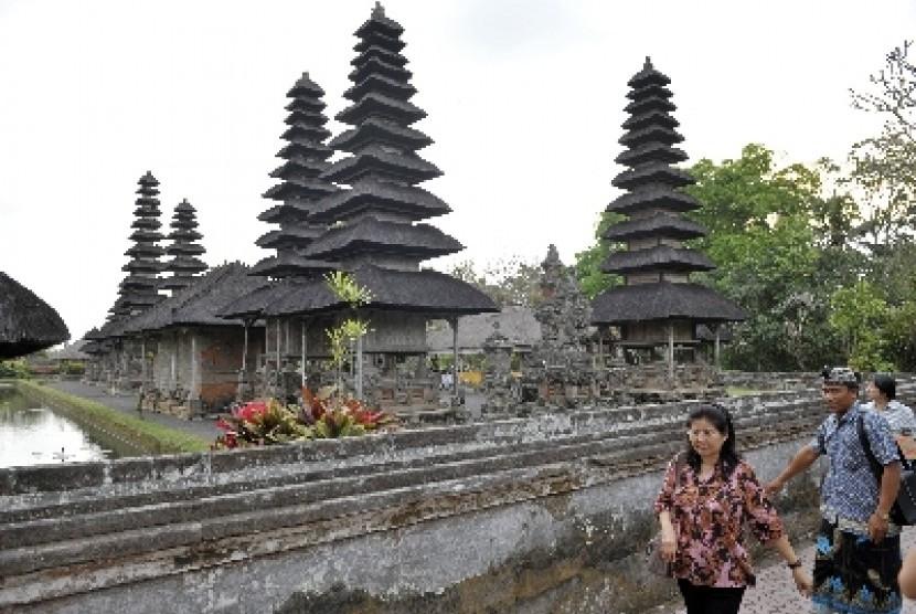 Seorang pemandu wisata mengarahkan wisatawan saat berkunjung ke Pura Taman Ayun, Badung, Bali