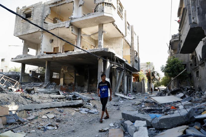 Seorang pemuda Palestina berjalan di antara puing-puing sebuah bangunan yang runtuh setelah terkena serangan udara selama perang 11 hari antara penguasa Hamas Gaza dan Israel Mei lalu, di Kamp Pengungsi Maghazi, Jalur Gaza tengah, Senin, 12 Juli 2021.