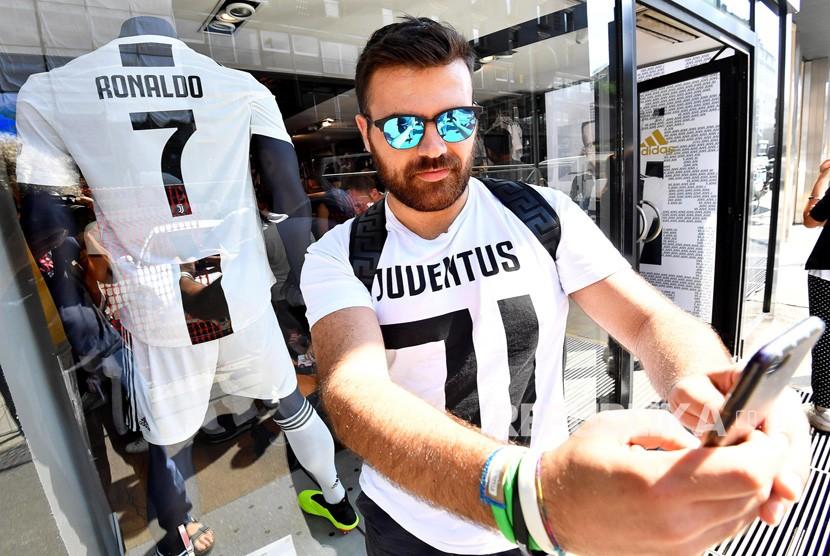 Seorang pendukung Juventus mengambil selfie dengan kaos Cristiano Ronaldo di luar toko Juventus di Milan, Italia (11/7).