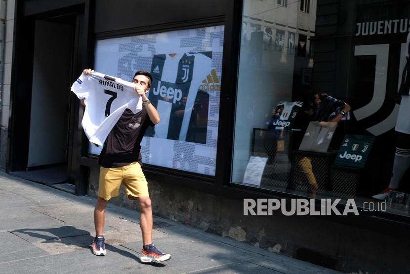 Seorang pendukung Juventus menunjukkan kaos Cristiano Ronaldo di luar toko Juve di via Garibaldi, Turin (11/7).