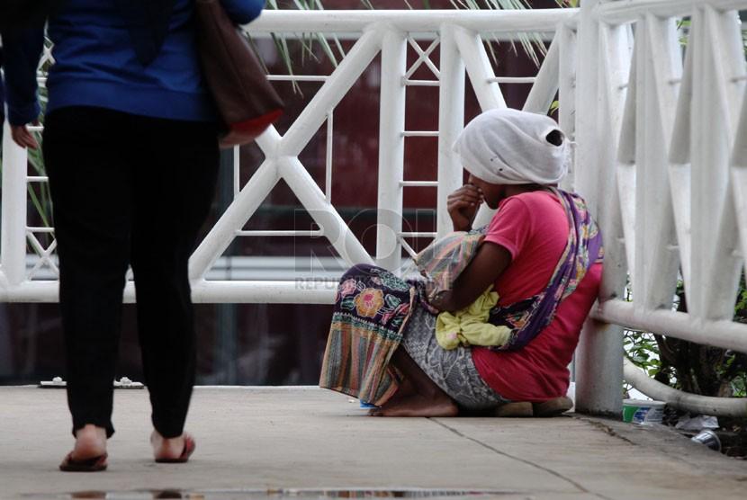 Seorang pengemis beraksi meminta sumbangan dari para pejalan kaki di Jembatan Penyeberangan Orang (JPO) Sarinah, Jakarta Pusat, Rabu (12/3). (Republika/Yasin Habibi)