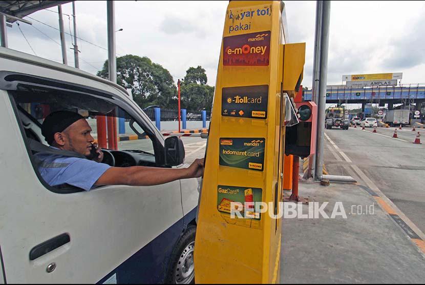 Seorang pengemudi mobil pengguna jalan tol bertransaksi menggunakan kartu elektronik non tunai ketika akan keluar dari tol. ilustrasi