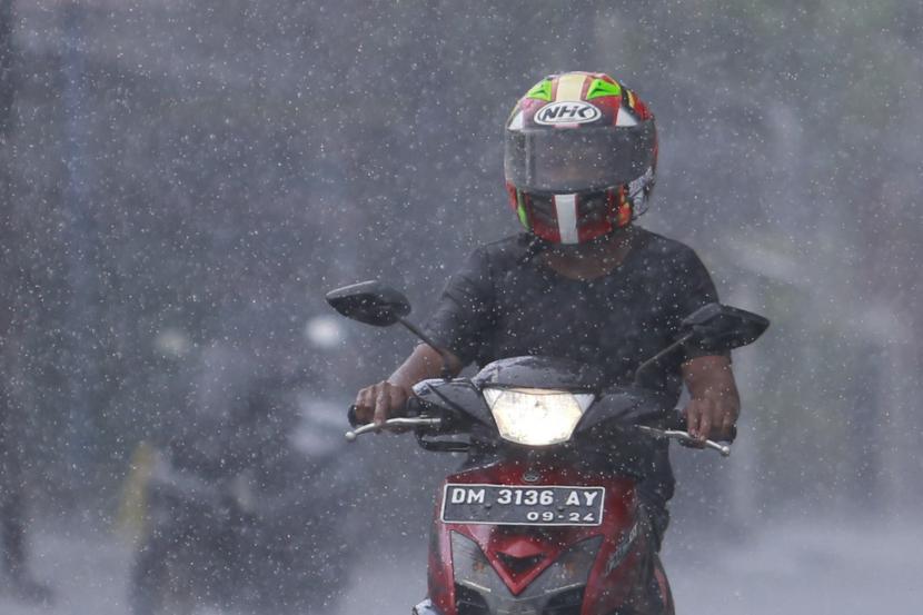 Seorang pengendara motor menerjang hujan deras yang mengguyur Kota Gorontalo, Gorontalo, Kamis (15/4/2021). Pemerintah Provinsi Gorotalo mengimbau warga untuk mengantisipasi potensi terjadinya badai Siklon Tropis Surigae yang menurut prediksi BMKG dapat menyebabkan gelombang tinggi mencapai satu hingga dua meter di perairan utara Gorontalo, serta potensi hujan lebat di sejumlah wilayah.
