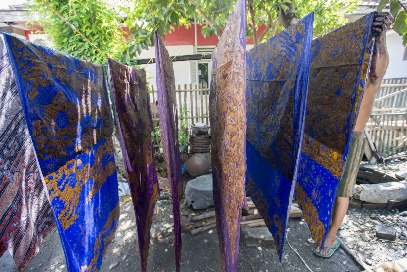 Seorang pengrajin batik menjemur kain batik usai diwarnai di salah satu  rumah di Centra Batik Tulis 1cb13b7978