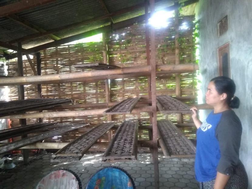 Seorang pengrajin tahu tempe di Blok Bungkul, Kelurahan Bojongsari, Kecamatan/Kabupaten Indramayu menunjukkan rak tahu dan tempe yang kosong, Senin (22/2). Mereka memutuskan mogok tiga hari sebagai bentuk protes mahalnya harga kedelai.