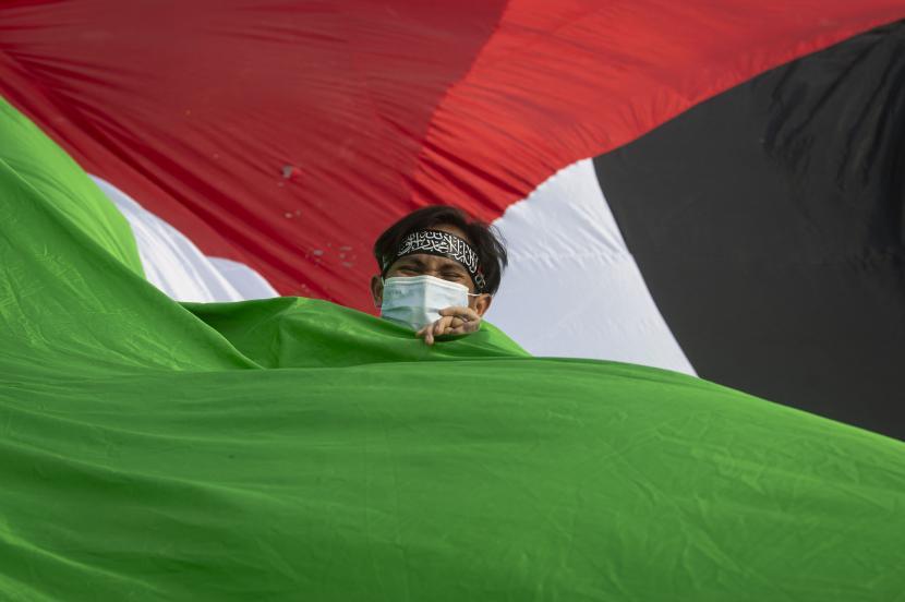 AWG Kutuk Pawai Provokatif Rezim Baru Zionis Israel. Foto ilustrasi: Seorang pengunjuk rasa membawa bendera Palestina saat aksi damai solidaritas mendukung Palestina.