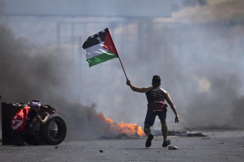 Seorang pengunjuk rasa mengibarkan bendera Palestina selama bentrokan dengan pasukan Israel di pos pemeriksaan Hawara, selatan kota Nablus, Tepi Barat, Jumat.  BSKAP DPR mendukung sikap Pemerintah mengutuk pengusiran warga Palestina