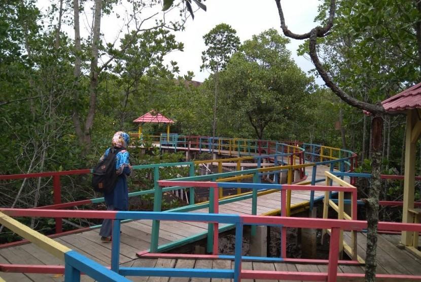 Seorang pengunjung berjalan di atas tracking mangrove di Desa Langge, Kabupaten Gorontalo Utara, Kamis (25/8).