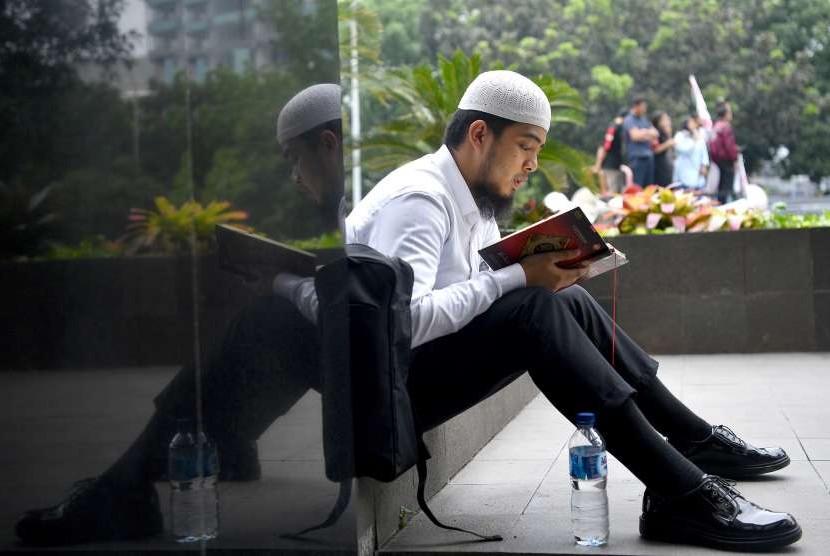 Seorang pengunjung membaca Alquran. (ilustrasi)