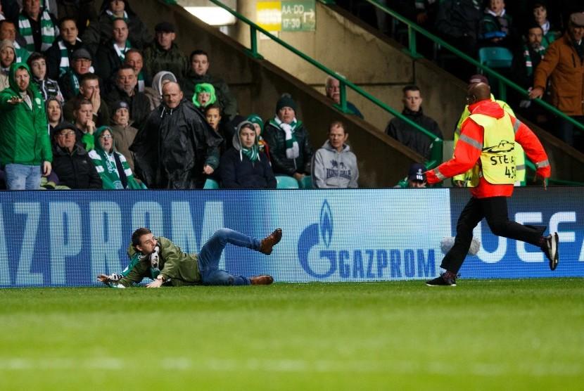 Seorang penonton (kiri) didekati oleh petugas keamanan (kanan) ketika laga antara Celtic dan Paris Saint-Germain di Celtic Park, Glasgow, Skotlandia, 12 September 2017.