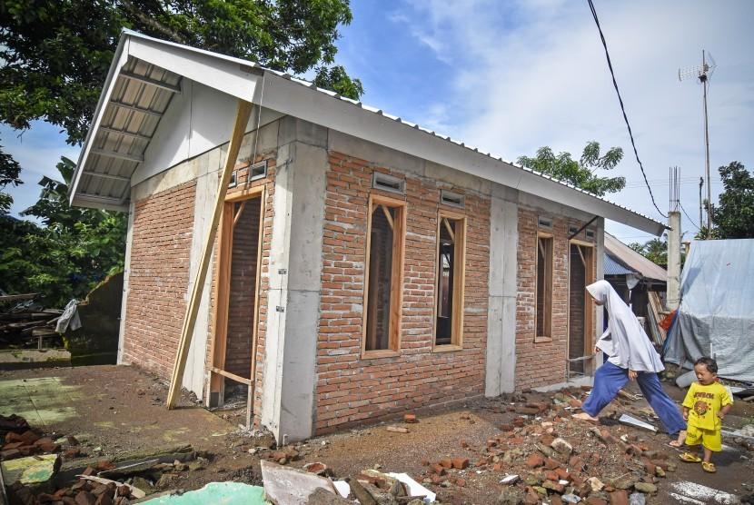 Seorang perempuan berjalan dekat bangunan Rumah Instan Sederhana Sehat (RISHA) untuk korban gempa di Desa Kekait, Kecamatan Gunungsari, Lombok Barat, NTB, Selasa (29/1/2019).