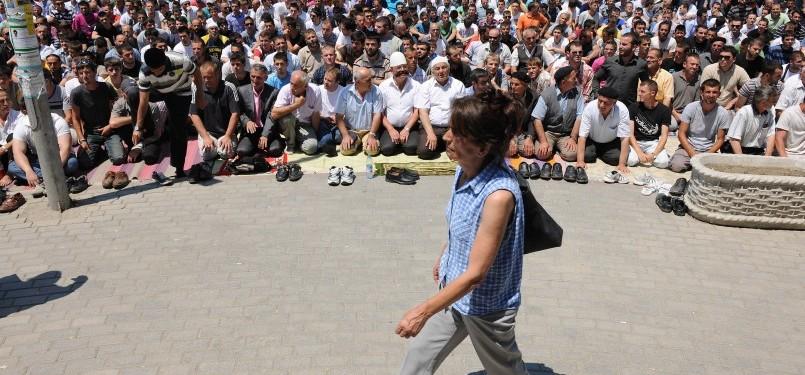 Seorang perempuan melenggang di hadapan ratusan jamaah shalat Jumat di jalan. Muslim Kosovo memprotes pemerintah ingin dibangunkan masjid yang representatif.