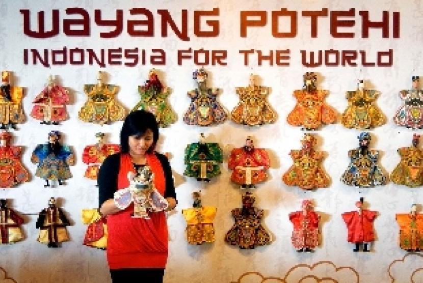 Seorang perempuan memainkan salah satu karakter wayang Potehi, di depan jajaran sejumlah karakter Wayang Potehi, yang dipamerkan di Lenmarc Mall Surabaya