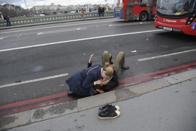 Seorang perempuan membantu korban luka di Westminster Bridge, London, Inggris, Rabu (22/3).