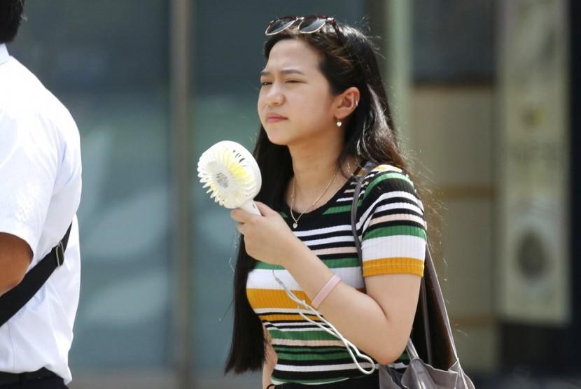 Seorang perempuan mengusir panas dengan kipas portable.