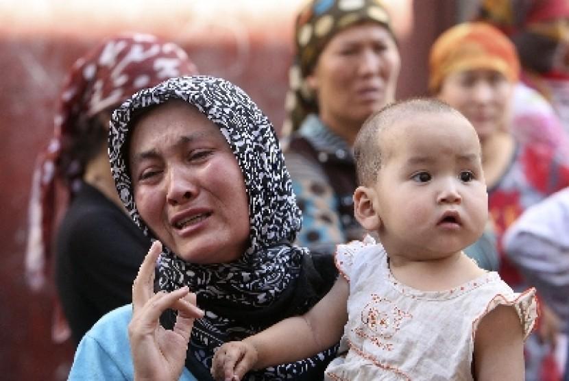 Seorang perempuan Muslim Uighur menangis setelah memprotes kekerasan yang dilakukan aparat keamanan.
