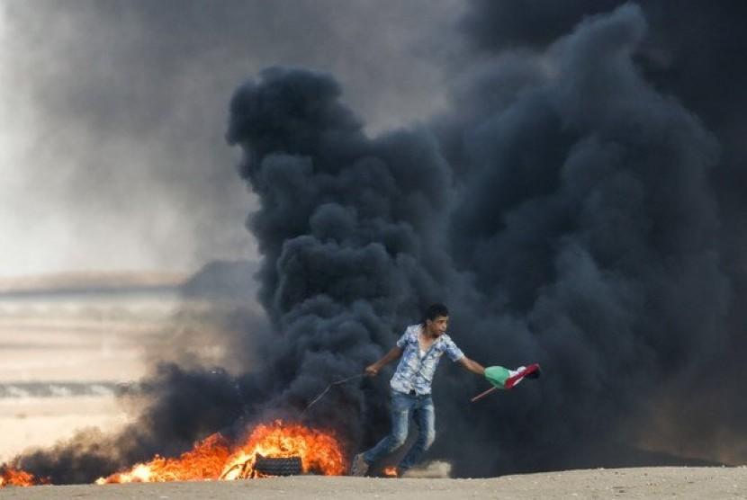 Seorang perempuan Palestina berlari membawa bendera Palestina dan menghindari serangan gas air mata dari tentara Israel.