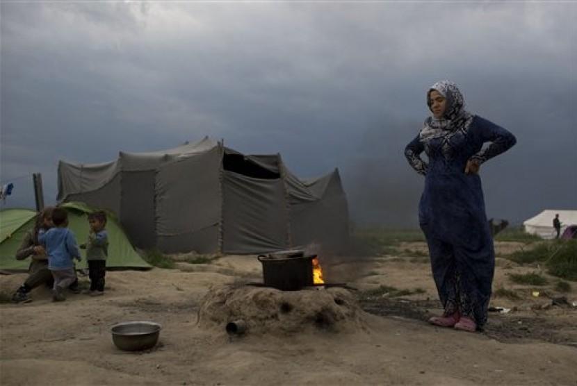Seorang perempuan Suriah memasak di kamp pengungsi di Idomeni, Yunani, Selasa, 10 Mei 2016.