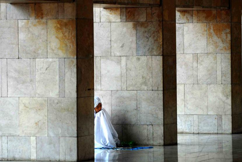 Seorang perempuan tengah khusyuk berdoa usai melaksanakan ibadah Shalat Dzuhur di Masjid Istiqlal, Jakarta, Senin (23/7). (Agung Supriyanto/Republika)
