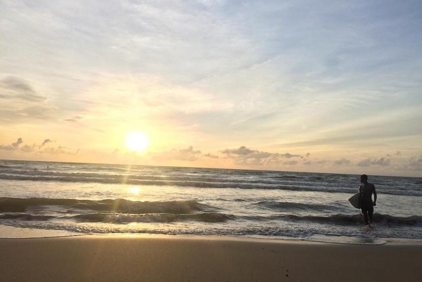 Seorang peselancar sedang berselancar di Pantai Carita, Banten, saat matahari terbenam, Sabtu (29/12). Sepekan setelah dihantam tsunami, aktivitas di Pantai Carita perlahan-lahan mulai pulih.