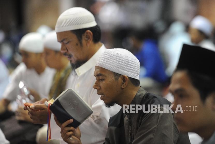 Seorang peserta Aksi Bela Islam III membaca alquran usai menunaikan ibadah shalat subuh berjamaah di Masjid Istiqlal, Jakarta, Jumat (2/12).