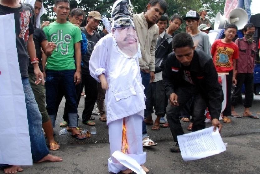 Seorang peserta aksi bersiap membakar simbolis bupati Musi Banyuasin saat menggelar unjuk rasa di depan Kementrian Aparatur Negara, Jakarta, Senin (7/2). Aksi yang diadakan oleh Aliansi Masyarakat untuk Institusi (Amunisi) ini menuntut Bupati Musi Banyuasi