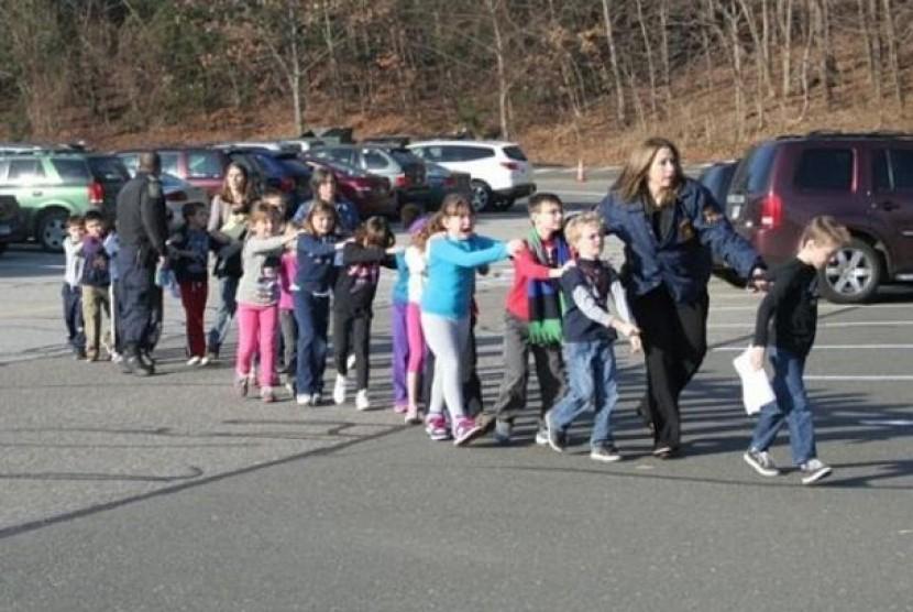 Seorang petugas keamanan mengawal murid-murid Sekolah Dasar Sandy Hook, Connecticut, AS, ke tempat aman, usai insiden penembakan di sekolah tersebut, Jumat (14/12/2012) menewaskan 26 orang.